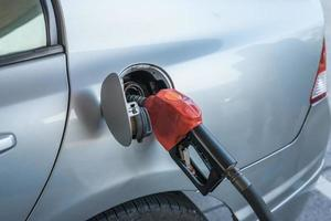 Pumping gasoline fuel in car at gas station photo