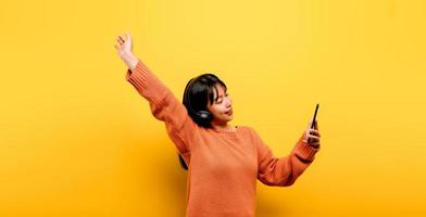 Asian woman happily using the phone and listening to music photo