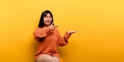 Asian girl Pretty wearing an orange casual dress on yellow background photo