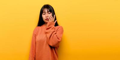 Cute Asian girl smiling on yellow background photo