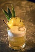 Pineapple mango tropical rum fruity cocktail drink in bar photo
