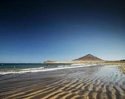 El Medano tourist beach and Montana Roja famous landscape in Tenerife Spain photo