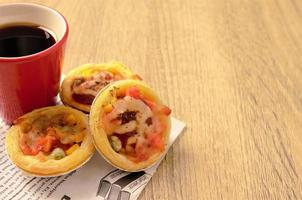 Egg tart pizza stack with coffee cup on wooden table backgrounds photo