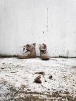 Antigua bota militar sobre fondo de pared blanca foto