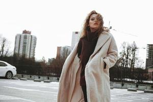 A girl with red curly hair in white coat poses on outdoor parking photo