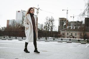 A girl with red curly hair in white coat. City construction photo