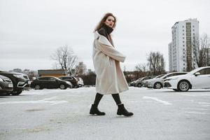 A girl with red curly hair in white coat poses on outdoor pa photo