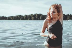 Young beautiful woman standing in the water. photo
