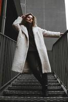 A girl with red curly hair in a white coat poses on the parking stairs photo