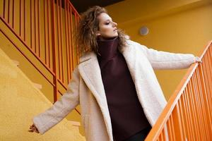 A girl with red curly hair in a white coat poses on the yellow parking photo