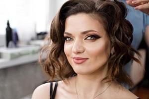 The hairdresser makes a hairstyle with curls to a beautiful brunette photo