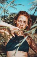 Woman in bikini on a tropical beach with plants photo