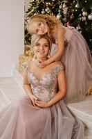 hija abrazando a su madre mientras está sentada en el árbol de navidad foto