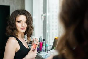 Portrait of elegant woman with curly hair looking at reflection photo
