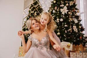 hija abrazando a su madre mientras está sentada en navidad foto