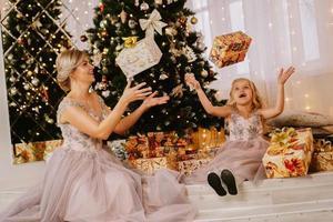 madre e hija sentadas cerca del árbol de navidad foto