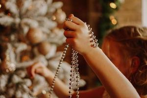 Girl decorates the christmas tree with beads photo