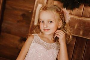 Chica con aretes de pelo largo y rubio en vestido rosa foto