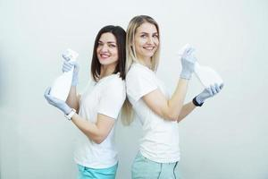 dos mujeres sostienen una botella de spray - antiséptico o detergente como pistolas foto