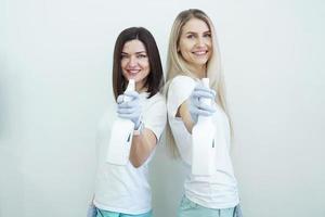 Two women hold spray bottle - antiseptic or detergent like guns photo