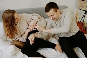 joven pareja enamorada está acostada en la cama, sonriendo y jugando foto