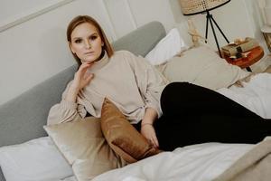 mujer vestida con suéter beige sentada en la cama foto