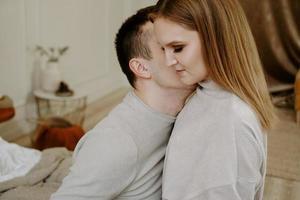 bonita pareja amorosa en la cama juntos. ellos se abrazan y sonríen foto