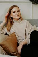 Woman dressed in beige sweater sitting on bed photo