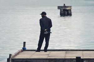 Sorong, West Papua, Indonesia 2021- A man standing alone on the wooden pier photo