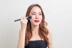 Portrait beautiful woman with makeup brush photo