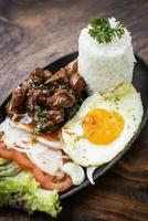 Cambodian traditional Khmer beef Lok Lak meal on wooden table photo