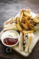 Classic gourmet club sandwich with fries on wooden board photo