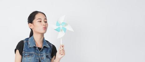 juguetes de molino de viento de papel y mujer adolescente. adolescente con palo de rueda de viento foto