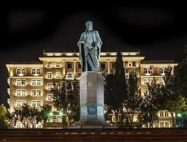 Nizami Square estatua histórica en el casco antiguo de la ciudad de Bakú, Azerbaiyán en la noche foto