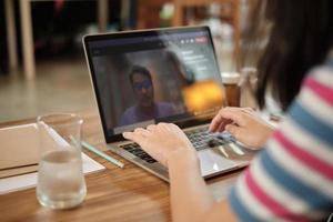 mujer asiática que usa la computadora portátil para trabajar desde casa y reuniones en línea. foto