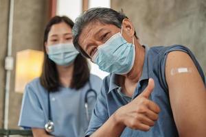 Paciente anciano con mascarilla pulgar hacia arriba cuando está vacunado. foto