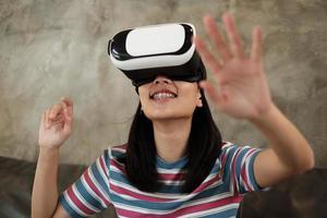 mujer asiática con auriculares vr, viendo la simulación virtual 3d. foto