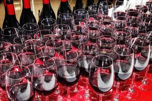 Glasses and bottles of red wine on cocktail party buffet table photo
