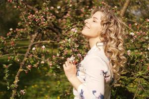 Romantic young woman in the spring garden among apple blossom. photo
