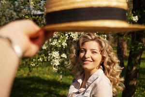 Smiling summer woman with straw hat in park photo