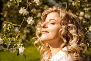 mujer joven romántica en el jardín de primavera entre flor de manzano. foto