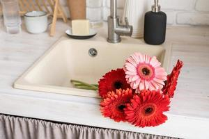 Red and pink gerbera daisies in a kitchen sink. Rustic kitchen photo