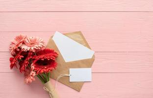 Flores de margarita gerbera roja, sobre y etiqueta en blanco en rosa foto