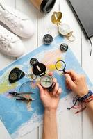 Top view woman planning a trip, holding compass and magnifying glass photo