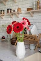 Red and pink gerbera daisies in a white vase on a wooden kitchen photo