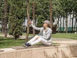 Woman outdoors taking selfie on her mobile phone photo