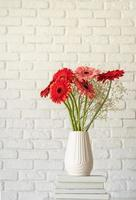 Bright gerbera daisies in white vase on stack of white books photo
