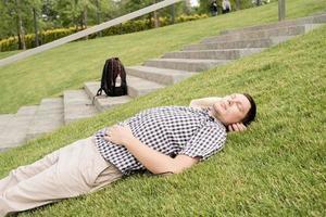 joven pensativo sentado en la hierba en el parque foto