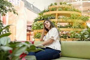 mujer joven, sentado, en, el, sofá, en, el, centro comercial foto