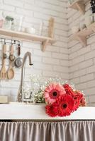 Red and pink gerbera daisies in a kitchen sink photo